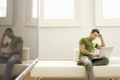 Man Using Laptop On Sofa In Modern Apartment - stock photo