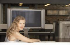 Young Woman In Living Room With Plasma Television In Background - stock photo