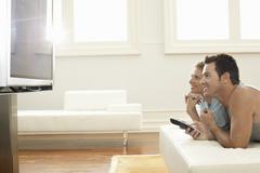 Couple Watching Plasma TV At Home Stock Photos