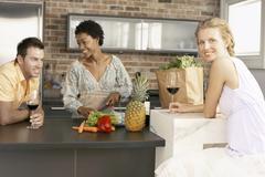 Young Woman With Friends Preparing Food In Kitchen - stock photo