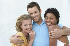 Young Man With Arms Round Two Female Friends Stock Photos