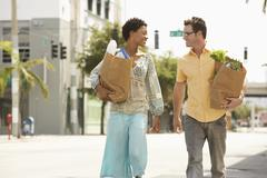 Stock Photo of Happy Couple With Groceries Walking On Street
