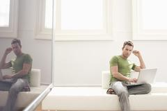 Stock Photo of Young Man Using Laptop In Modern Apartment