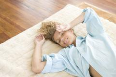 Young Woman Lying On Rug At Home Stock Photos