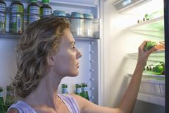 Woman Looking For Food In Refrigerator Stock Photos