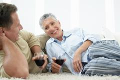 Couple Drinking Wine On Rug In Home Stock Photos
