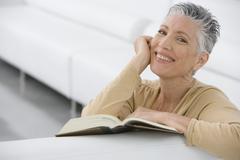 Hymyilevä vanhempi nainen käsittelyssä varaa sohvalla - stock photo
