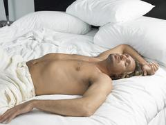 Stock Photo of Man Sleeping In Hotel Bedroom