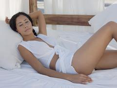 Sexy Woman Relaxing In Four-Poster Bed Stock Photos