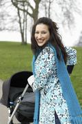 Mother Walking With Baby Carriage In Park Stock Photos
