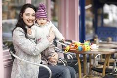Mother Holding Baby On Lap Sitting In Outdoor Cafe - stock photo