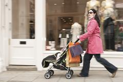 Mother Pushing Stroller By Clothes Shop Stock Photos