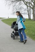 Happy Mother Walking With Baby Carriage In Park Stock Photos