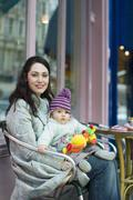 Mother Holding Baby On Lap Sitting In Outdoor Cafe Stock Photos