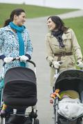 Mothers With Strollers In Park Having Chat - stock photo