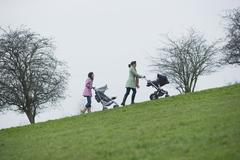 Stock Photo of Mothers Pushing Baby Strollers Uphill In Park