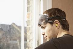 Man Wearing Goggles And Earplugs While Looking Out Of Window - stock photo
