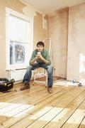 Man Holding Coffee Mug On Step Ladder In Unrenovated Room - stock photo