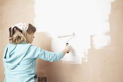 Woman Painting Wall With Paint Roller - stock photo