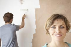 Happy Woman With Man Using Paint Roller On Wall - stock photo