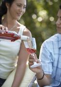Woman Pouring Wine Into Boyfriend's Glass - stock photo