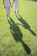 Low Section Of Couple Holding Hands - stock photo