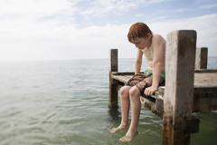 Shirtless Boy Sitting On Jetty Stock Photos