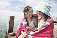 Girls Wrapped In Towel Sitting On Jetty - stock photo