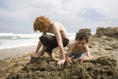 Boys Playing In Sand At Beach Stock Photos