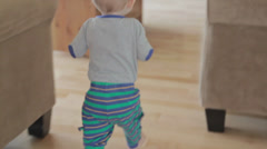 A toddler running to play the piano Stock Footage