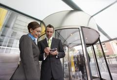 Businesspeople Using PDA In Front Of Revolving Door - stock photo