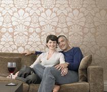 Happy Couple Sitting On Sofa - stock photo