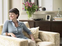 Happy Woman Sitting On Armchair Stock Photos