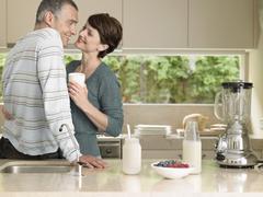 Woman Holding Milkshake While Looking At Husband In Kitchen - stock photo