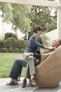 Woman Sitting On Man's Lap In Lawn Stock Photos
