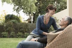 Happy Woman Sitting On Man's Lap In Lawn - stock photo