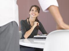 Stock Photo of Businesswoman Sitting At Desk Looking At Male Colleague