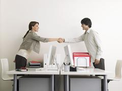 Business People Shaking Hands Over Desks - stock photo