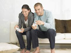 Couple Playing Video Game On Sofa Stock Photos
