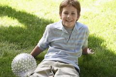 Teenage Boy Sitting In Lawn With A Ball - stock photo
