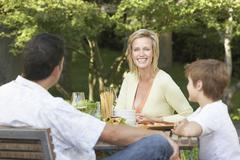 Family Having Meal At Picnic Table - stock photo
