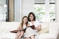 Mother And Daughter Reading Book In Living Room Stock Photos