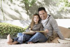 Father And Daughter Sitting With Photo Album - stock photo