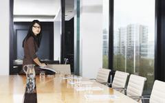Stock Photo of Businesswoman Sitting On Table In Boardroom