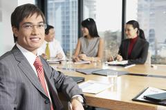 Businessman With Colleague In Boardroom Stock Photos