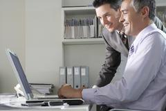 Stock Photo of Businessmen Using Laptop At Desk