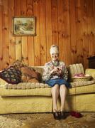 Senior Woman Sitting On Sofa Knitting - stock photo