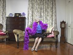 Senior Woman Wearing Feather Boa In Living Room Stock Photos