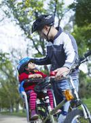 Girl On Bicycle Looking At Father - stock photo
