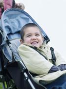 Stock Photo of Happy Boy Sitting On Pram